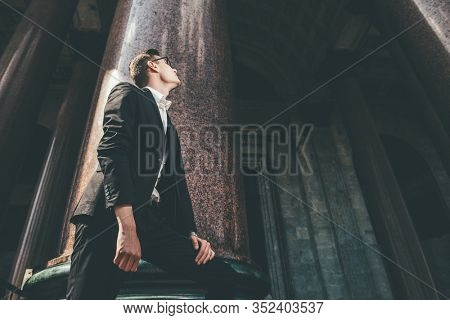 A portrait of a goodlooking young student looks at the large columns of the building. Men's beauty, fashion.