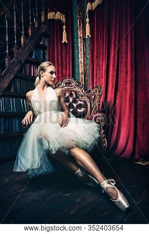 A full length portrait of an elegant refined female ballet dancer posing in the vintage interior. Talent, fashion for ballet dancers.