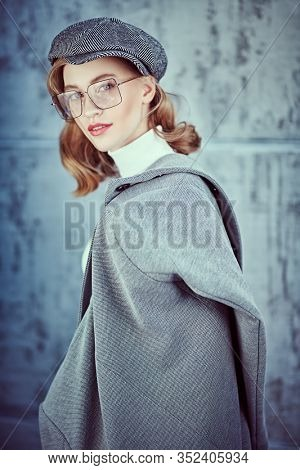 Romantic young woman with natural makeup and beautiful wavy blonde hair wearing autumn clothes and trendy glasses. Beauty, fashion concept. Optics and eyewear style.