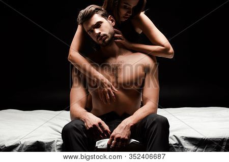 Sensual Woman Touching Shirtless Man Sitting On Bed Isolated On Black