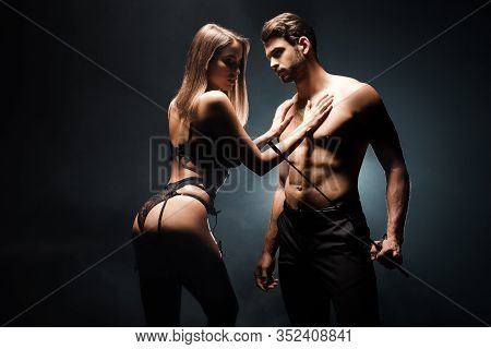 Shirtless Man Holding Flogging Whip Near Submissive Woman In Underwear Standing On Black