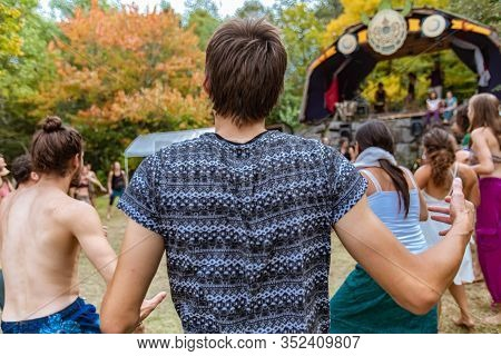 A Twenty Something Boho Guy Is Seen From The Back, With Unkempt Brown Hair And Blue Printed T Shirt,