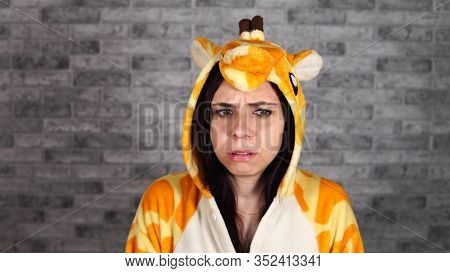 A Funny Woman In A Big Pajamas Of Giraffe Is Showing A Fright On A Brick Background. A Brunette Was