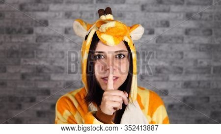 A Funny Young Woman In A Big Pajamas Of Giraffe Is Smiling And Doing Silencing Gesture With Index Fi