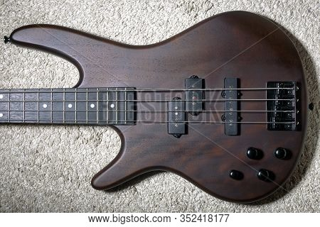 Left-handed Bass Guitar With Four Strings. Popular Rock Musical Instrument. Top View Of Brown Electr
