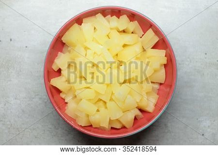 Pineapple Slices In A Red Ceramic Plate On A Gray Background With Marble Cracks And Specks. The Conc