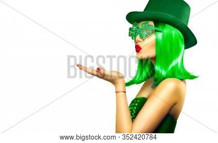 St. Patrick's Day leprechaun model girl in green hat, funny clover sunglasses holding product, pointing hand, isolated on white background, kiss. Patrick Day pub party, celebrating. Green beer. Ads