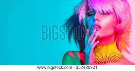 Fashion model woman in colorful bright lights, portrait of beautiful party girl with trendy make-up, manicure and haircut. Art design of disco dancer, colorful make up. Over colourful vivid background