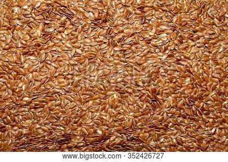 Background Made Of Organic Flax Seeds. Flaxseeds Backdrop. Linseed