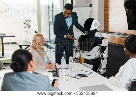 Handsome African American Businessman Pointing With Hand At Robot Near Multicultural Colleagues In C