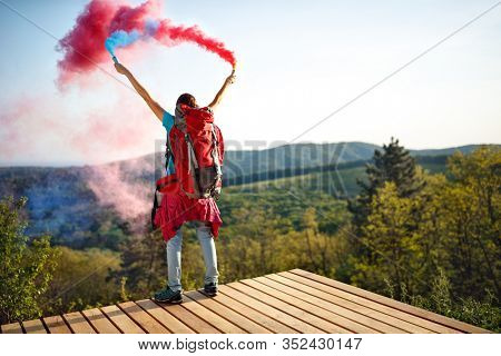Hiker female waves with smokes torch and sends signals to hiker friends