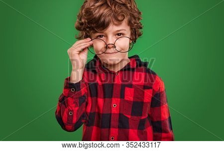 Cute Clever Youngster In Checkered Shirt Putting On Spectacles And Looking At Camera Against Green B