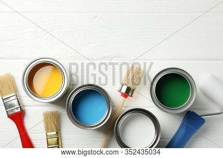 Different Paints, Brushes And Roller On Wooden Background, Top View