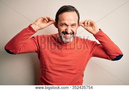 Middle age hoary man wearing casual orange sweater standing over isolated white background Smiling pulling ears with fingers, funny gesture. Audition problem