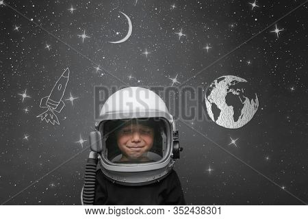 Small child wants to fly an in space wearing an astronaut helmet