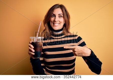 Young beautiful brunette woman drinking glass with cola refreshment using straw very happy pointing with hand and finger