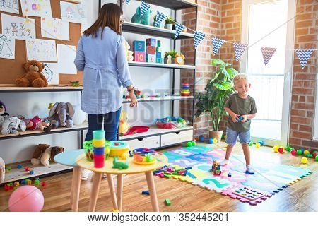 Young caucasian child playing at playschool with teacher. Mother and son at playroom around toys.