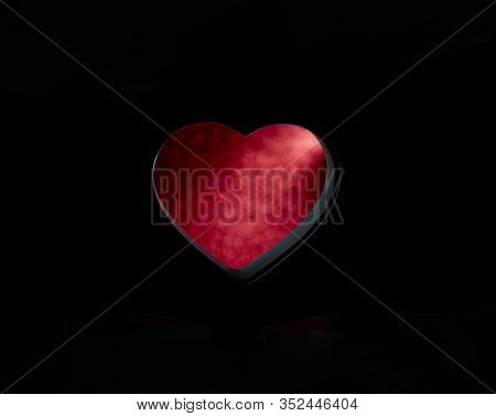 Blurred Red Out Of Focus Bokeh Of Shiny Red In A Hole On A Black Background In The Shape Of A Heart.