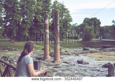 A Woman Near The Great Marble Column Of Old Building Tempel. Tourist At The Museum Excavations Of Th