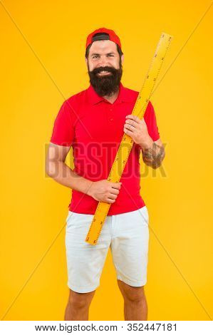 Back To School. Bearded Man With Big Measuring Instrument. Measuring His Height With Ruler. Gauge An