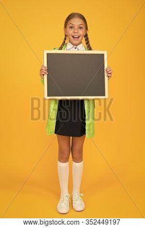 Schoolgirl Wear Raincoat Hold Blank Chalkboard Copy Space. Waterproof Fabric For Comfort. Rainproof