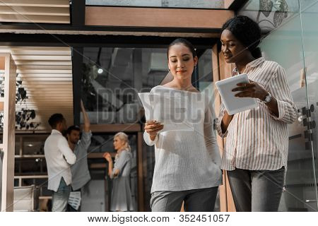 Young African American And Asian Businesswomen With Digital Tablet And Documents Standing In Office