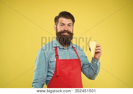 Cheese Maker. Bearded Man In Apron Hold Piece Cheese. Cheese Making Techniques. Online Shopping. Gou
