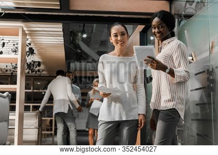 Smiling Multicultural Businesswomen With Digital Tablet And Documents Looking At Camera While Collea