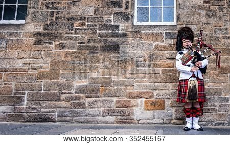 Scotland, United Kingdom - May 30, 2019: Scottish Piper In Traditional Costume Plays On Edinburgh St