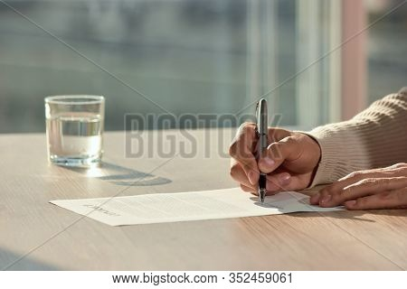 Male Hands Writing Signing New Contract. Business Man Hand Holding Pen Writing On Papers Signing Con