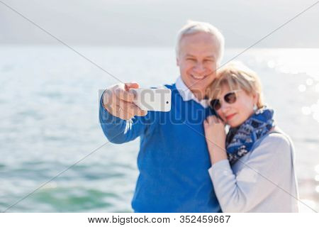 Senior Couple Take Photo Selfie At Sea Beach Outdoor. Happy Man And Woman Using Mobile Phone. Travel