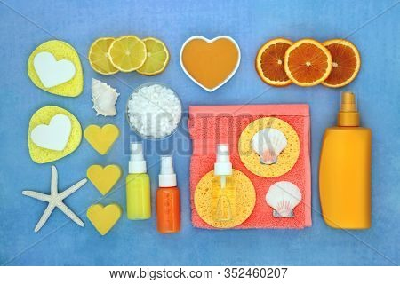 Summer spa beauty treatment with fresh blood orange fruit, after sun lotion, moisturising creams & oil, ex foliation salts, soap & cleansing products. Flat lay on blue background.