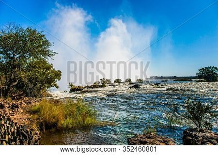 Grand Victoria Falls. Victoria is a waterfall on the Zambezi River in South Africa. Giant cloud of mist rose above the waterfall. Fantastic walk after the rainy season. Concept of  photo tourism
