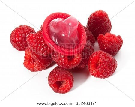 Unwrapped Color Condom With Fruit Flavor And Raspberries On White Background. Macro Shot. Safe Sex C