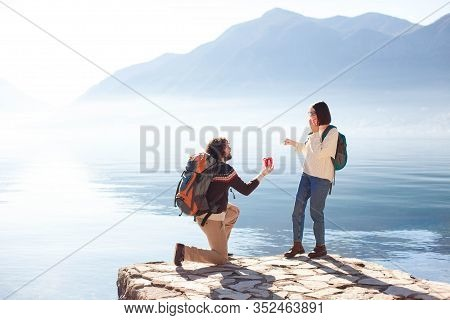 Young Man Proposing To Woman On His Knee And Giving Gift Box. Couple At Winter Sea Beach By Mountain