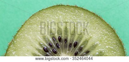 Closeup Of A Kiwi Fruit In Front Of A Green Background