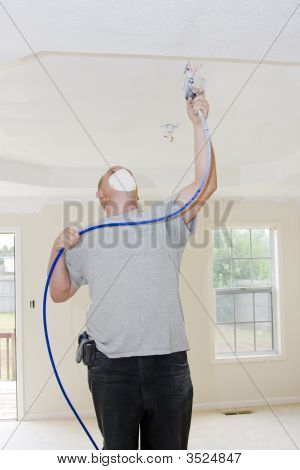 Contract painter updating colors of walls and painting ceilings bright white to speed up selling of home poster