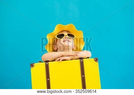 Portrait Of Happy Child With Yellow Suitcase Against Blue Background. Kid Having Fun On Summer Vacat