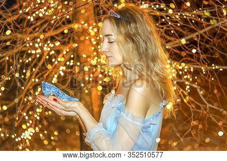Beautiful Princess In Blue Long Dress On The Luminous Yellow Tree Background With Blue Crystal Shoe