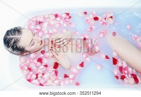Young Sexy Girl Taking A Milk Bath With Rose Petals Closeup