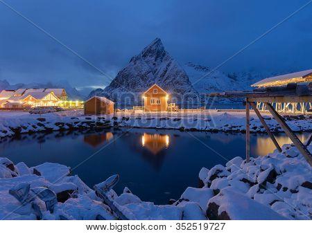 Home, Cabin Or House At Night, Norwegian Fishing Village In Reine City, Lofoten Islands, Nordland Co