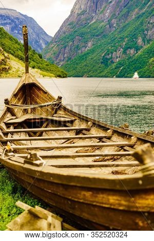 Old Wooden Viking Boat On Seashore In Norwegian Nature And Ferryboat On Fjord. Mountains And Sognefj