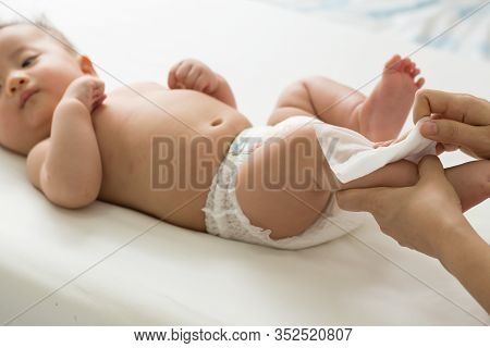Mom Cleaning Up And Wipe Body Baby By Wet Tissue When Changing Nappies Or Diaper And Wiping The Hand