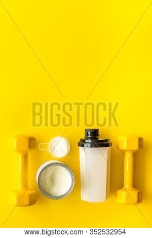 Sport Nutrition. Whey Protein, Shaker, Dumbbells On Yellow Background Top-down Flay Lay Copy Space