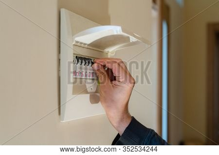Hand Switching Power Switch On A Fusebox. Close Up Of Electrician Checking Fuse Box Knob
