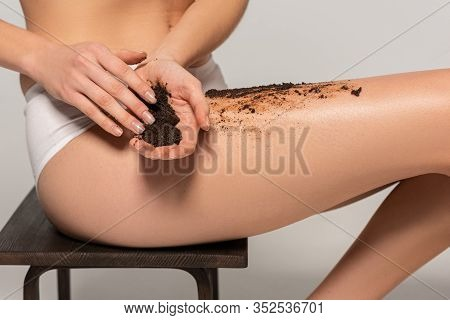 Cropped View Of Woman Applying Coffee Exfoliant While Sitting On Chair, On Grey