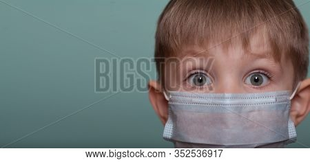 Child Boy With Large Blue Eyes In A Medical Mask, On A Blue Background, Close-up, Isolate. Place For