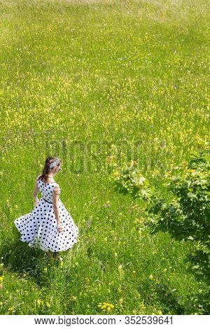 Girl With A White Vintage 50´s Dress And Hair Band Is Walking Through A Wildflower Meadow, Backview