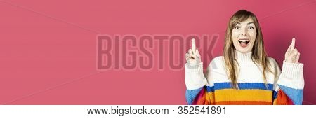 Young Girl In A Knitted Sweater, Surprised, Show A Gesture Of Hands, Crossed Fingers For Luck And Lu
