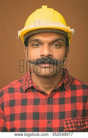 Indian Man Construction Worker With Mustache Against Brown Background